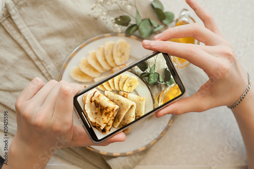 Fototapeta Food blogger creating content. Pancakes with bananas and honey on white plate  obraz