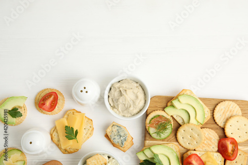 Fototapeta Different snacks with salted crackers on white wooden table, flat lay. Space for text obraz