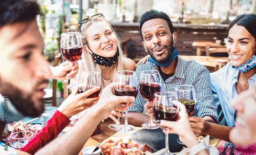 Canvas Print Multiracial people toasting wine at restaurant garden wearing open face mask - N