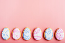 Easter Frosted Cookies In Shape Of Egg On Pink Background. Flat Lay With Copy Space.