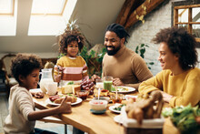 Happy Black Family Enjoying In Meal At Dining Table At Home.