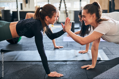 Obraz Joyful young women doing planking and supporting each other - fototapety do salonu