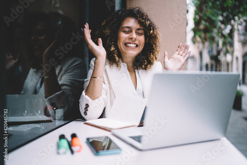 Joyful female freelancer with curly hair surprised with received web results via text email message on laptop computer, happy IT professional respond emotionally to online news rejoicing near netbook
