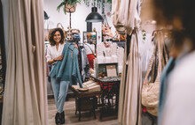 Caucasian Woman With Hanger Trying Clothes Near Mirror In Merchandise Boutique Mall, Cheerful Hipster Girl Posing Near Glass Looking At Own Reflection While Choosing Brand Clothing On Shopping