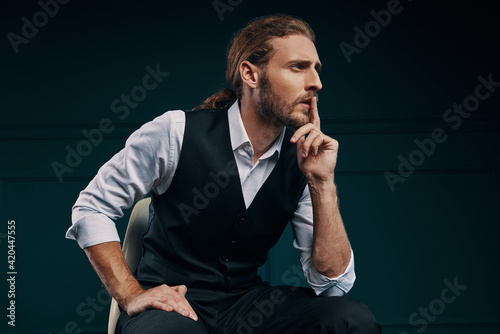 Thoughtful young man in elegant shirt looking away and keeping finger on lips wh Fototapeta