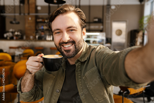 Foto White man smiling and drinking coffee while taking selfie photo