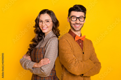 Portrait of attractive cheerful glad couple coworkers back to back folded arms isolated on bright yellow color background