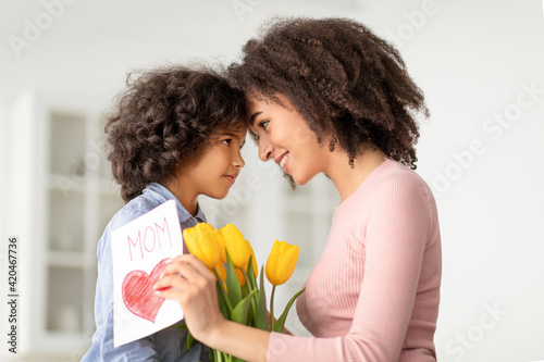 Fotografija Black girl greeting mom with tulips and card