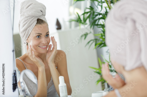 Obraz na płótnie woman performing her skincare routine in front of the mirror