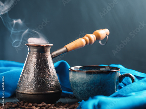 Fototapeta A cup of aromatic coffee, roasted coffee beans. Beautiful blue cup and jezva obraz