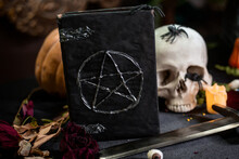 Focus On A Black Book With A Pentagram Lying On A Black Table Against A Background Of A Skull And Pumpkin. Halloween Magic Ritual Concept.