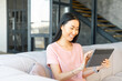 Asian woman with black straight hair using modern grey digital tablet while sitting in loft-style apartment, smiling, touching the screen, reading pleasant message from boyfriend, relaxing on sofa