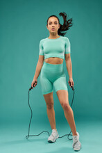 Attractive Young Woman In Sportswear Using Skipping Rope