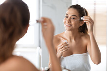 Woman Applying Face Serum Using Dropper Caring For Skin Indoors