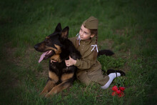 Portrait Of A Girl With Pigtails With A Dog Avcharka In A Military Uniform In The Spring In Nature