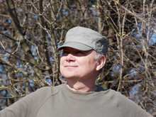 Portrait Of An Adult Smiling Man In A Cap On The Background Of Nature