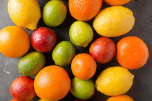 Citrus Fruits On Gray Abstract Background. Orange, Lemon, Grapefruit, Mandarin, Lime. Mixed Festive Colorful Tropical And Citrus Fruit. Healthy Eating Photo Concept. Copyspace