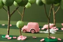 A Pink Car Mini Model Running On Street