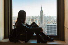 Woman Looking At New York Cityscape From A Rooftop