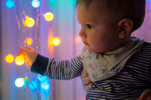 Baby Boy Playing With Xmas Lamps