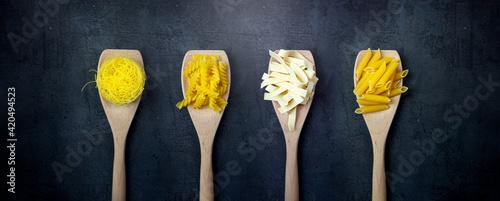 Fototapeta Rodzaje makaronów na drewnianych łyżkach na ciemnym tle. Baner symbolizujący włoską kuchnię.  obraz
