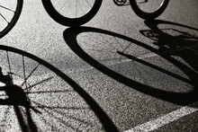 Road Cycling Racing Bike Abstract Backlit View Of Shadow Bicycle Wheel Racing Along Road In Bicycle Lane. Silhouette Of Front And Rear Road Bike On A Bright Modern Pavement