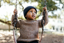 An Adorable Little Boy On A Park Swing