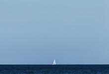 One Sailboat On The Sea Horizon