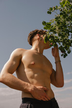 Portrait Of A Young Handsome Topless Guy With A Pearl Earring Hiding His Face In The Rose Bush In Front Of The Sky Background