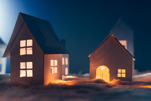 Close Up Of Handmade Small White Cardboard Houses With Illuminated Windows On Snowy.