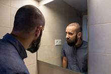 Man Looking In Front Of Mirror After The Hair Transplant Operation