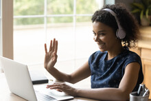 Ready To Start. Positive Biracial Teen Female In Headset Sit By Laptop Waving Hand To Camera Greet Teacher Tutor At Distant Video Lesson. Young Black Woman Student Learning Online Via Web Conference