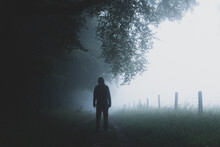 A Man Silhouetted On A Countryside Path. On A Foggy, Spooky Day