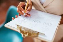 Crop Ethnic Businesswoman Making Notes In Calendar