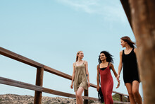 Young Diverse Girlfriends Walking On Wooden Path Against Sky