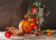 Still Life With Vegetables And Fruits. Pumpkins, Pepper, Apple, Tangerine, Samovar On A Dark Background High Quality Photo