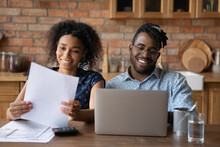 Affairs In Order. Happy Black Family Couple Engaged In Home Accounting Pay Bills Using Laptop. Young Afro American Spouses Check Review Financial Papers Feel Satisfied Glad Of Making Payments In Time