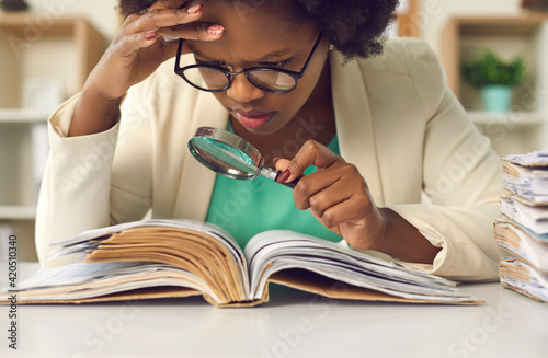 Fototapeta Closeup portrait of concentrated young african american woman auditor with magnifying glass scrutinizing financial documents at desk with paper folder pile in office. Investigation and audit checkup obraz