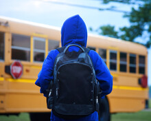 Boy Student Waiting In Front Of School Bus Outside