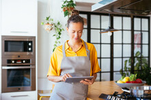 Relaxed Woman In Apron Surfing Tablet In Kitchen