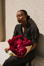 City Portrait Of A Beautiful Black Girl In A Polka Dot Dress With A Bouquet Of Peony Flowers
