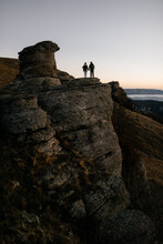 Couple Stands On The Edge Rock At Dawn
