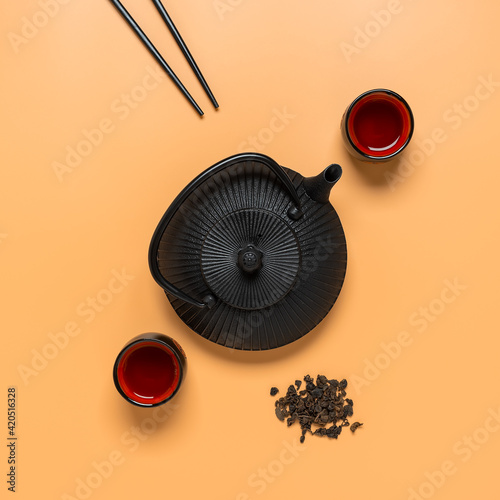 Fototapeta Creative layout made of traditional Asian tea ceremony. Black metal teapot, ceramic tea cups and chopsticks on pastel background. Top view. obraz na płótnie