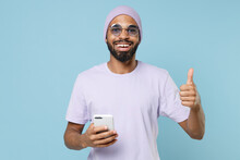 Young Smiling Unshaven Student Black African Man 20s Wear Violet T-shirt Purple Hat Glasses Using Mobile Cell Phone Show Thumb Up Like Gesture Isolated On Pastel Blue Color Background Studio Portrait.
