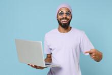Young Smiling Surprised Unshaven Student Black African Man 20s Wear Violet T-shirt Purple Hat Glasses Point Index Finger On Laptop Pc Computer Isolated On Pastel Blue Color Background Studio Portrait.