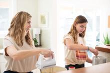 Teenage Girl And Her Mom Baking Cookies
