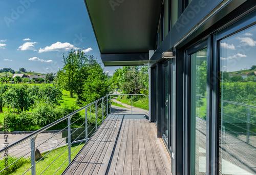 Fotografiet Fensterfront mit Holzterrasse an einem Einfamlienhaus im Grünen