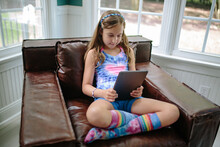 Beautiful Young Girl In A Tie Dye Shirt And Socks Using A Tablet