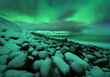 Aurora borealis over ocean. Northern lights in Teriberka, Russia. Starry sky with polar lights and clouds. Night winter landscape with bright aurora, stars, sea, snowy stones in blurred water. Travel