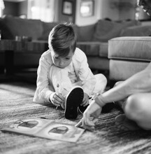 Young Boy Learning How To Tie His Shoes